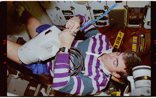 STS062-22-017 - STS-062 - Pilot Allen preparing vaccuum cleaner onboard Columbia