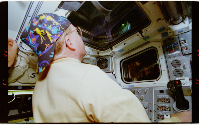 STS064-22-023 - STS-064 - Cdr. Richards peering out of aft flight deck windows