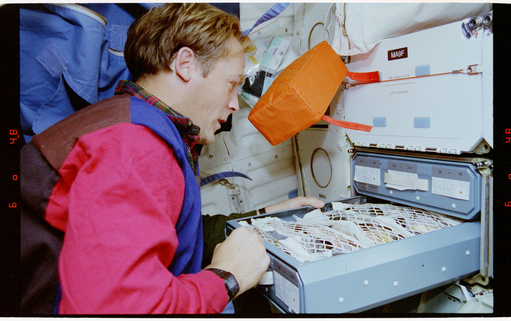 STS064-39-021 - STS-064 - PC Lee opening a middeck food locker