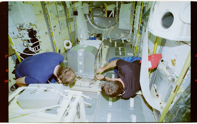 STS065-43-001 - STS-065 - Halsell and Hieb repair the HRM in the Spacelab center aisle