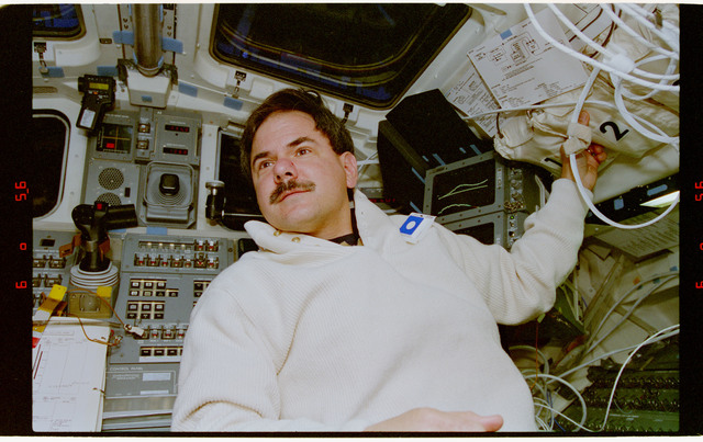 STS067-351-023 - STS-067 - DSO 488 - Parise in the flight deck wearing personal formaldehyde air sampler