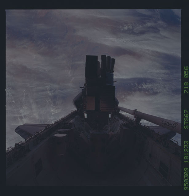STS067-718-056 - STS-067 - ASTRO-2 in payload bay backdropped by the Earth