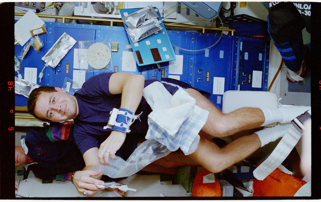 STS068-33-013 - STS-068 - STS-68 crewmembers perform various tasks onboard Endeavour's middeck