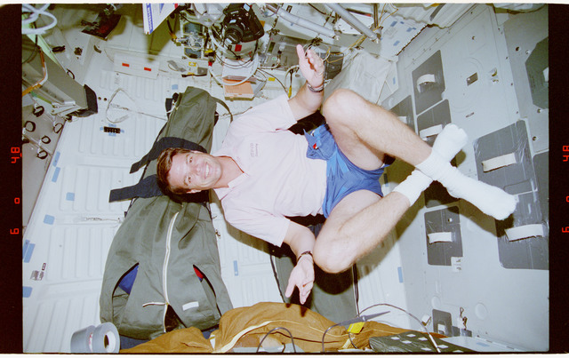 STS070-335-001 - STS-070 - Kregel and Weber float in the middeck in a yoga position