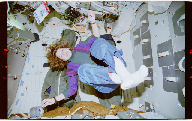 STS070-335-010 - STS-070 - Kregel and Weber float in the middeck in a yoga position