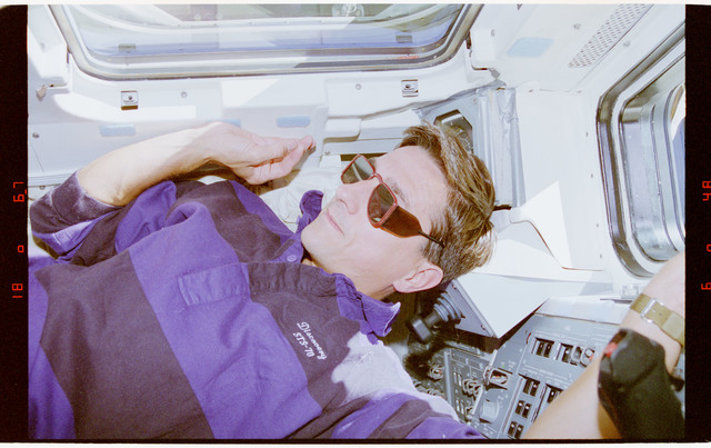 STS070-395-034 - STS-070 - Thomas takes a look out the overhead and aft flight deck windows wearing sunglasses