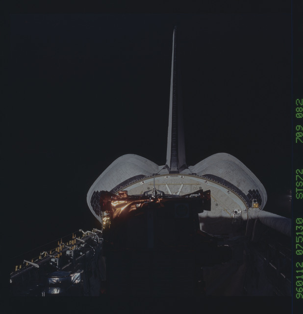 STS072-709-082 - STS-072 - Payload bay is in dark shadow while the shuttle tail and OMS pods are brightly lit
