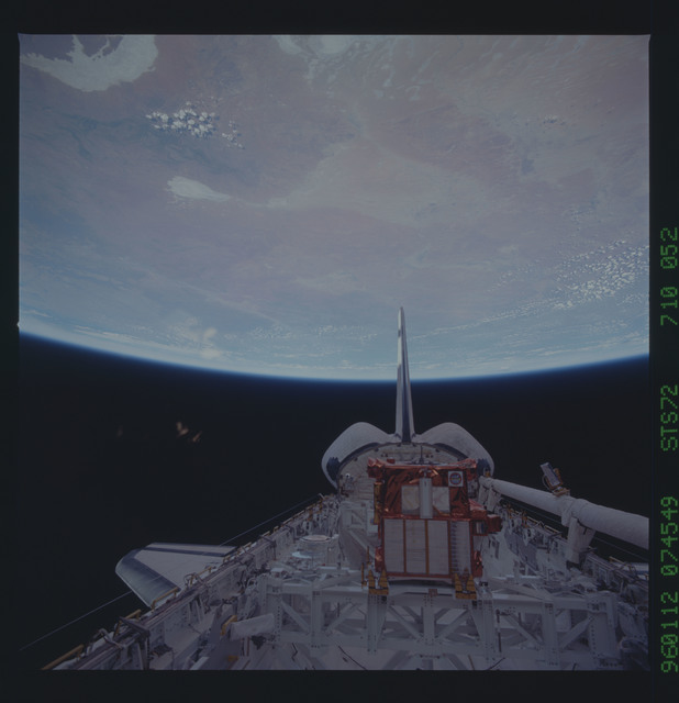 STS072-710-052 - STS-072 - Payload bay with OAST-Flyer berthed and the shuttle tail pointing to the earth limb