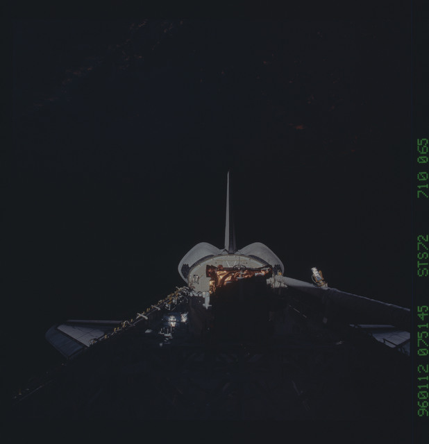 STS072-710-065 - STS-072 - Payload bay with OAST-Flyer berthed and the shuttle tail pointing to the earth