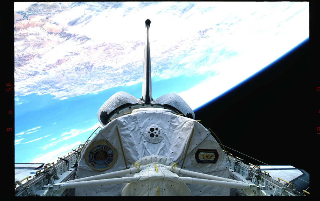 STS073-323-015 - STS-073 - Payload bay with Spacelab and tail against Earth's surface