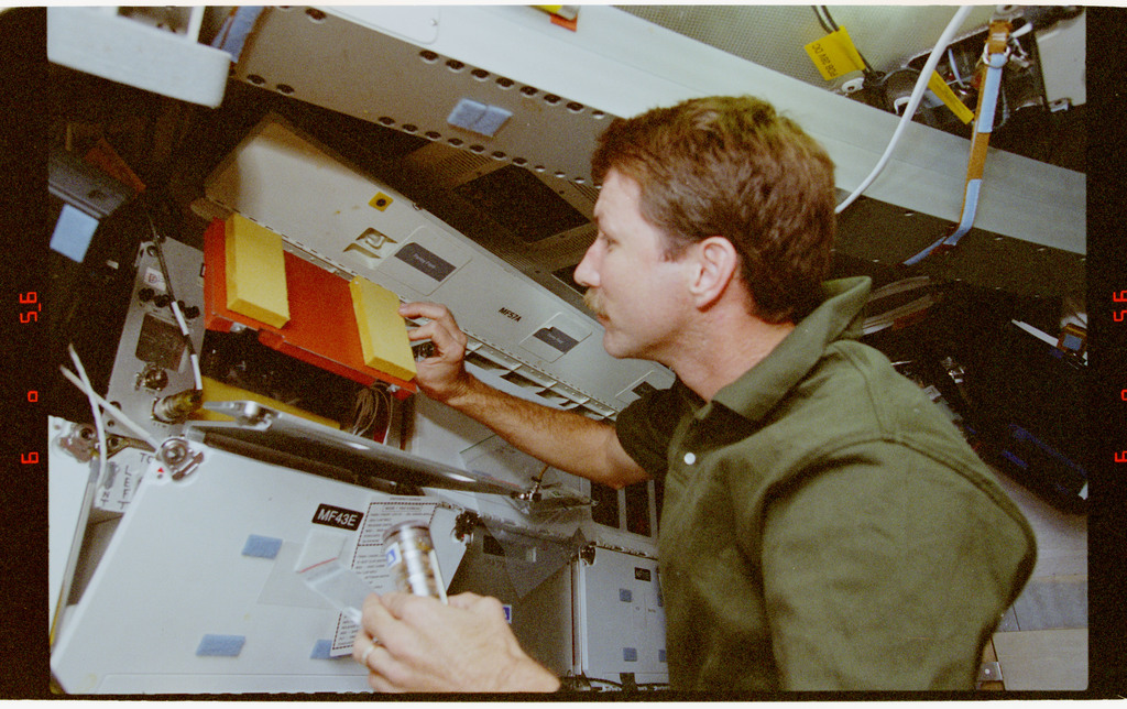 STS073-351-003 - STS-073 - PCG, Pilot Kent Rominger transfers protein crystal vials to Sacco in Spacelab