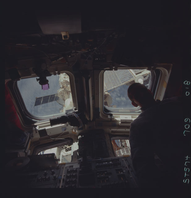 STS074-709-018 - STS-074 - STS-74 crewmember views Mir Space Station through aft flight windows