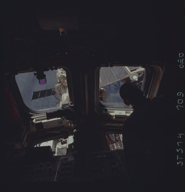 STS074-709-020 - STS-074 - STS-74 crewmember views Mir Space Station through aft flight windows