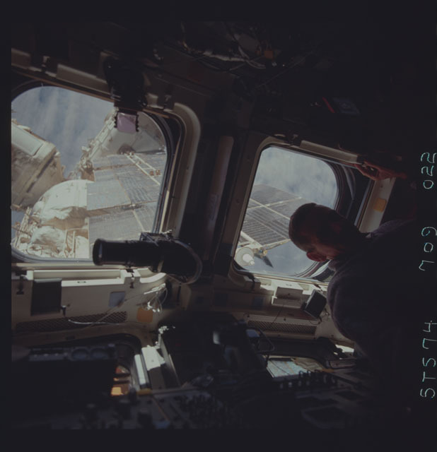 STS074-709-022 - STS-074 - STS-74 crewmember views Mir Space Station through aft flight windows