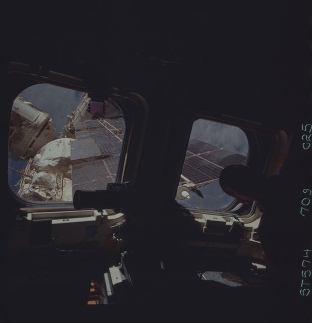 STS074-709-025 - STS-074 - STS-74 crewmember views Mir Space Station through aft flight windows