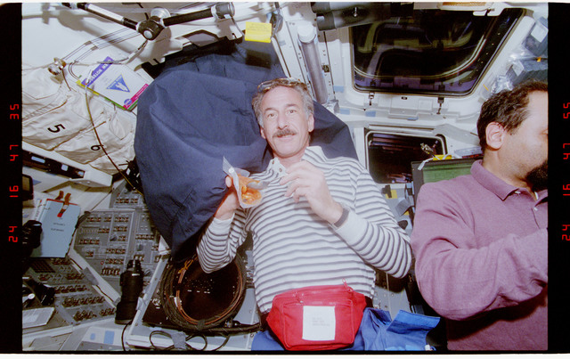 STS075-310-019 - STS-075 - Astronaut Hoffman eating his meal on the aft flight deck
