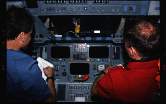 STS076-309-003 - STS-076 - Commander Kevin Chilton and Pilot Rick Searfoss review procedures in flight deck