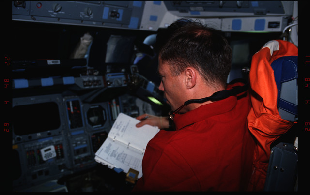 STS076-309-004 - STS-076 - Pilot Rick Searfoss review procedures in flight deck