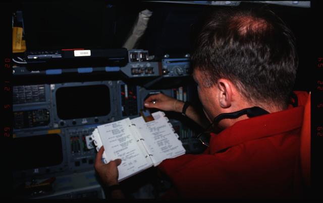 STS076-309-007 - STS-076 - Pilot Rick Searfoss review procedures in flight deck