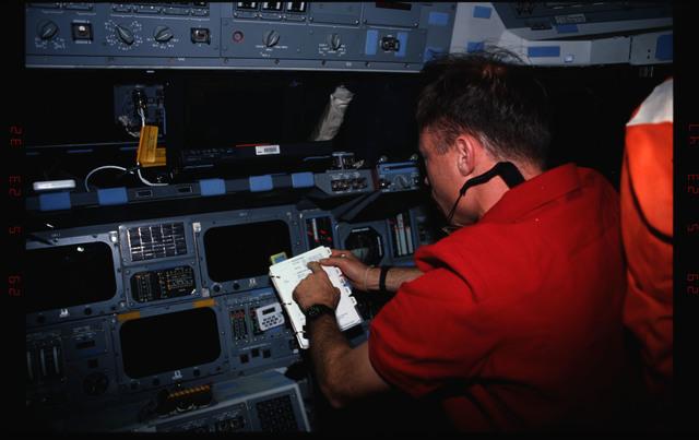 STS076-309-011 - STS-076 - Pilot Rick Searfoss review procedures in flight deck