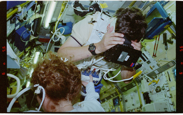 STS078-304-025 - STS-078 - COIS, Favier works with experiment assisted by Helms during LMS-1 mission