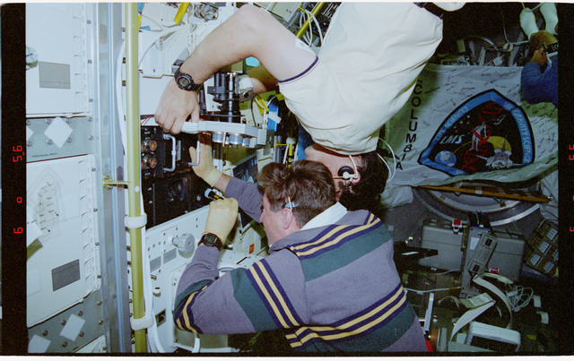 STS078-305-011 - STS-078 - BDPU, Henricks places new test chamber into experiment module in LMS-1 Spacelab