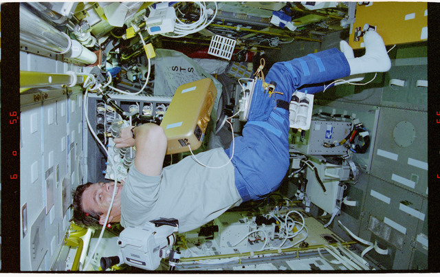 STS078-305-025 - STS-078 - UMS, Kregel works with syringe stowage cage in the Spacelab module on LMS-1