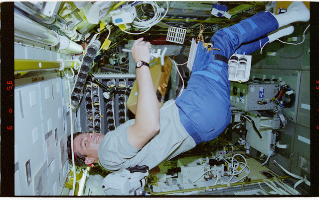 STS078-305-026 - STS-078 - UMS, Kregel works with syringe stowage cage in the Spacelab module on LMS-1