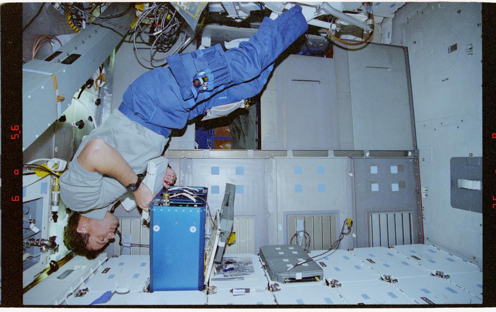 STS078-305-033 - STS-078 - AEM, Kregel checks the status of the middeck locker experiment