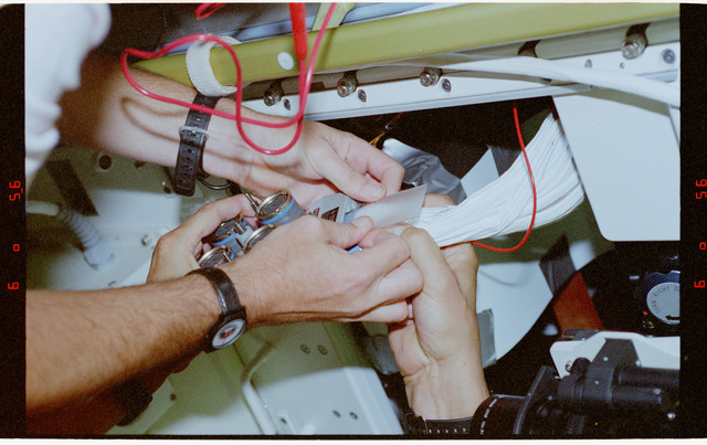 STS078-397-015 - STS-078 - BDPU IFM, Favier and Kregel repair a short in the experiment's wires