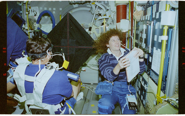 STS078-428-021 - STS-078 - COIS, Favier works with experiment assisted by Helms during LMS-1 mission
