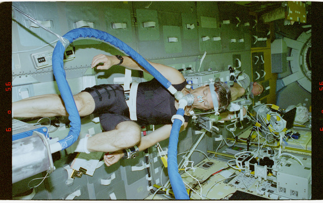 STS078-430-018 - STS-078 - ALFE, Thirsk exercises on Spacelab ergometer as Helms monitors