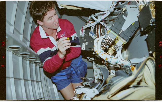 STS078-432-008 - STS-078 - Henricks examines the computer systems under the Spacelab floor