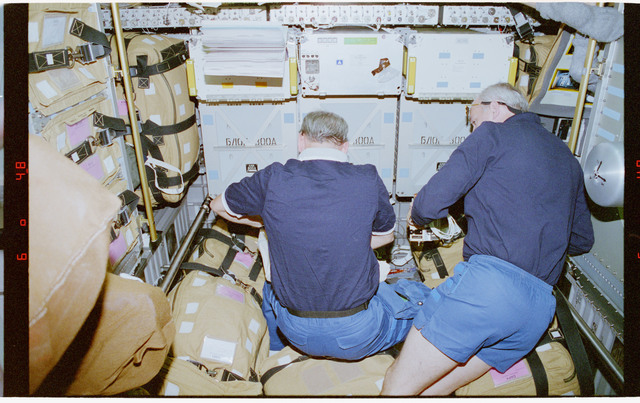 STS079-301-028 - STS-079 - Akers and Readdy review stowage items in Spacehab module