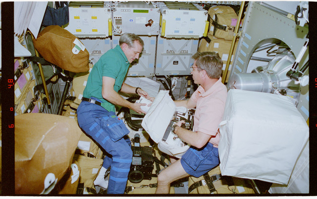 STS079-309-011 - STS-079 - Astronauts Akers and Blaha prepare stowage items for transfer