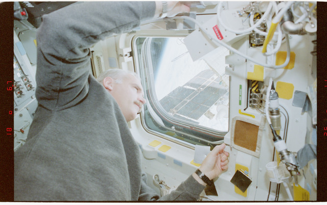 STS079-353-008 - STS-079 - STS-79 crew at aft flight deck overhead windows with Mir in background