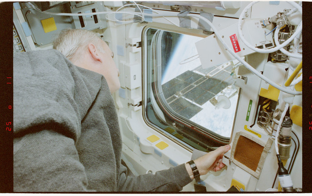 STS079-353-009 - STS-079 - STS-79 crew at aft flight deck overhead windows with Mir in background