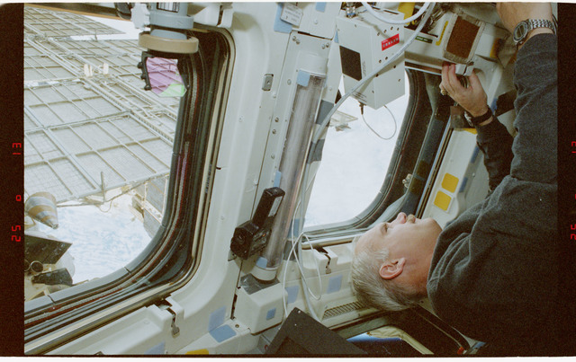 STS079-353-010 - STS-079 - STS-79 crew at aft flight deck overhead windows with Mir in background
