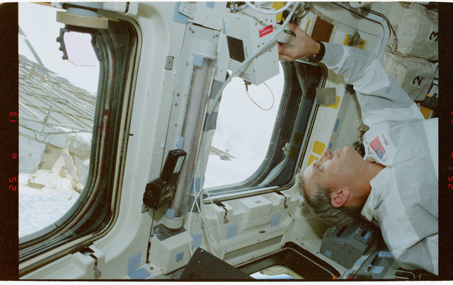 STS079-353-011 - STS-079 - STS-79 crew at aft flight deck overhead windows with Mir in background