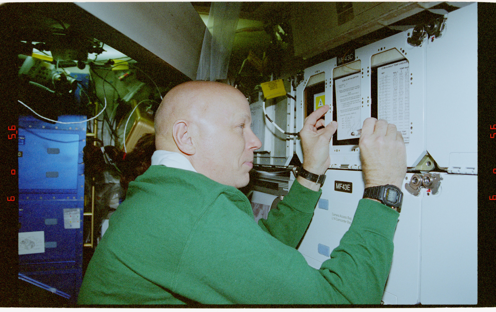 STS080-318-031 - STS-080 - CCM-A, Musgrave notes time and temperature on the middeck locker experiment