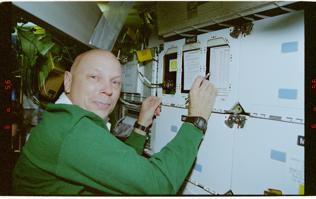 STS080-318-033 - STS-080 - CCM-A, Musgrave notes time and temperature on the middeck locker experiment