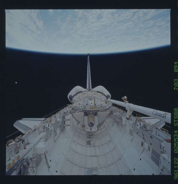 STS080-703-094 - STS-080 - View of the payload bay with shuttle tail pointing at the Earth limb
