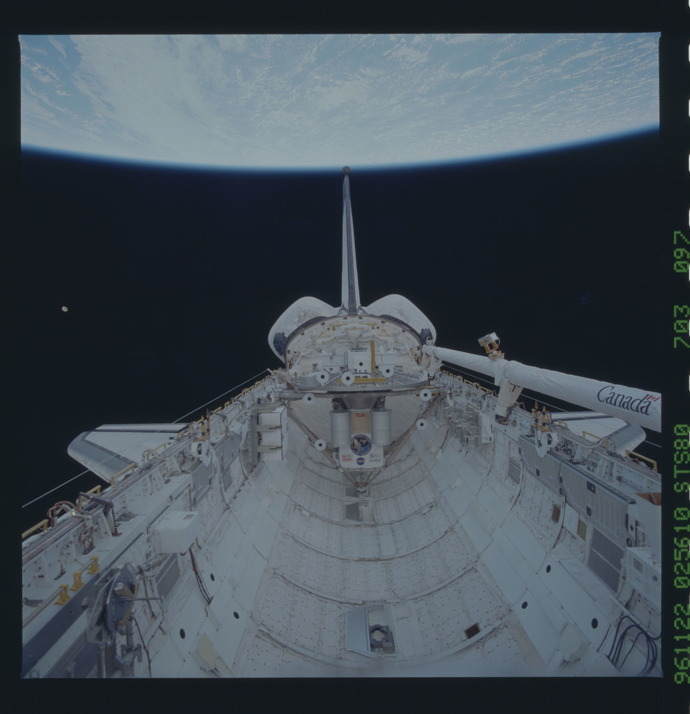 STS080-703-097 - STS-080 - View of the payload bay with shuttle tail pointing at the Earth limb