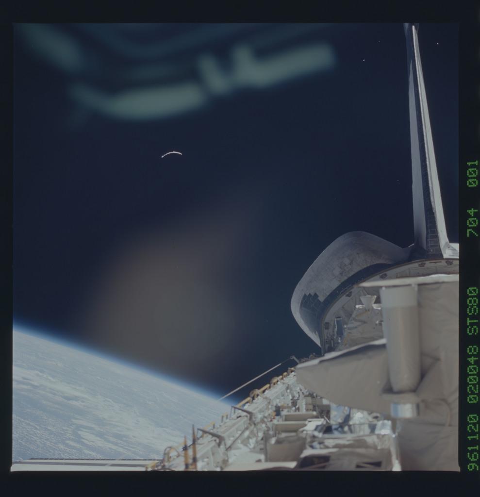 STS080-704-001 - STS-080 - A piece of debris floats up past aft flight deck window