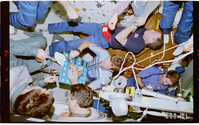 STS081-348-010 - STS-081 - STS-81 and Mir 22 crew share a barbecue dinner on the Atlantis's middeck