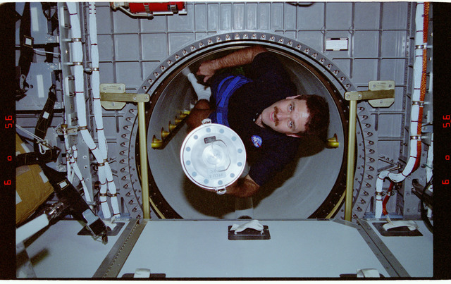 STS081-361-027 - STS-081 - MS Grunsfeld moves freezer unit through transfer tunnel to Spacehab