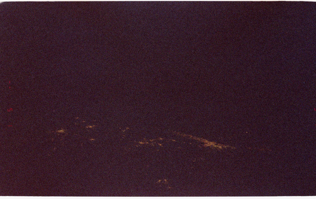 STS081-376-018 - STS-081 - City lights and sunset seen during STS-81 mission
