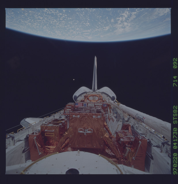 STS082-714-092 - STS-082 - Payload bay view with orbiter tail pointing at the Earth limb
