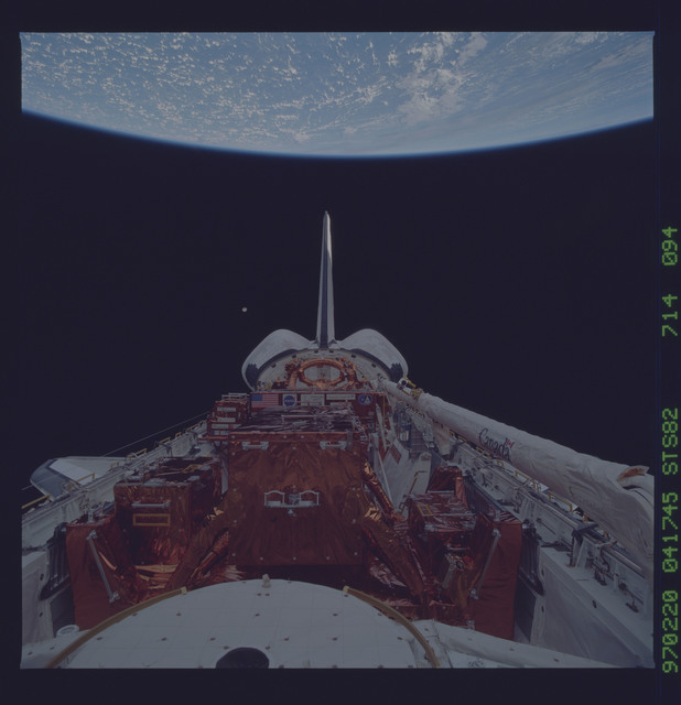 STS082-714-094 - STS-082 - Payload bay view with orbiter tail pointing at the Earth limb