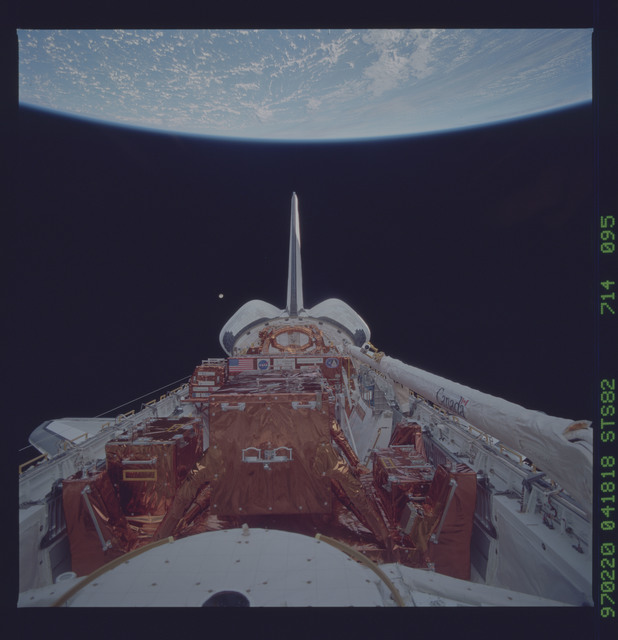 STS082-714-095 - STS-082 - Payload bay view with orbiter tail pointing at the Earth limb